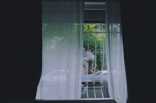 bílé závěsy v okně